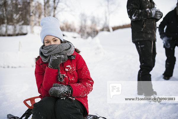 Schweden  Lappland  Hemavan  Junge Frau im Winter auf dem Schlitten sitzend