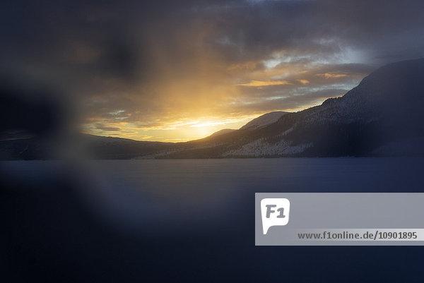 Schweden  Lappland  Hemavan  Sonnenuntergang über Bergen mit gefrorenem See im Vordergrund