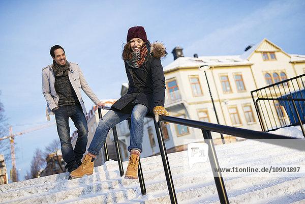 Schweden  Vasterbotten  Umea  Mann beobachtet junge Frau auf dem Geländer gleitend