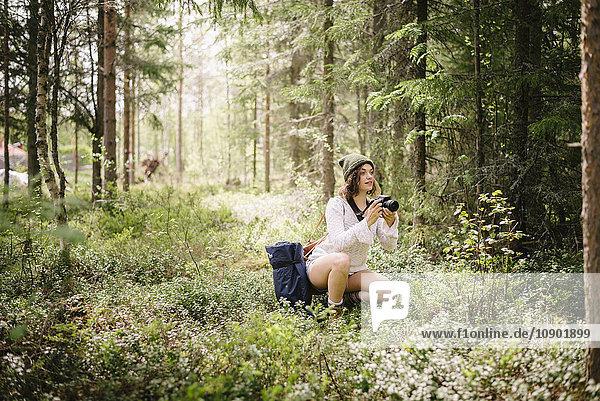 Schweden  Vasterbotten  Norrmjole  Junge Frau beim Fotografieren im Wald