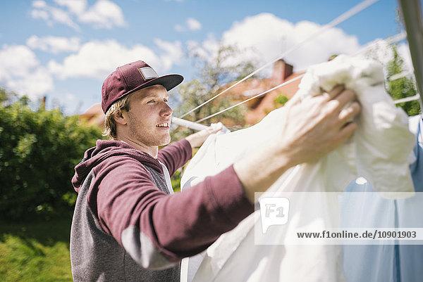 Schweden  Vasterbotten  Junger Mann beim Wäschewaschen