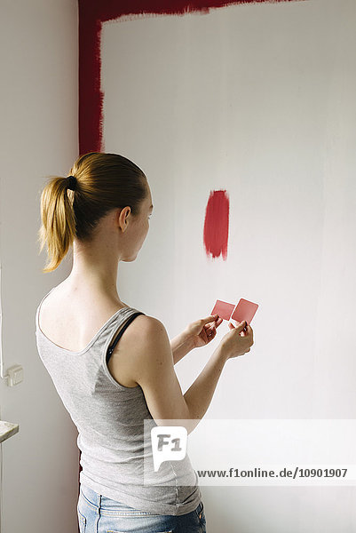 Schweden  Frau vergleicht Farbmuster gegen die Wand