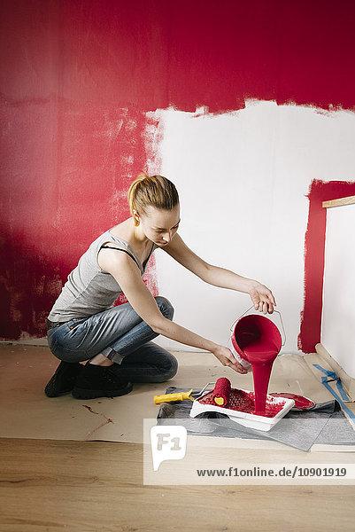 Schweden  Frau gießt Farbe in die Farbwanne