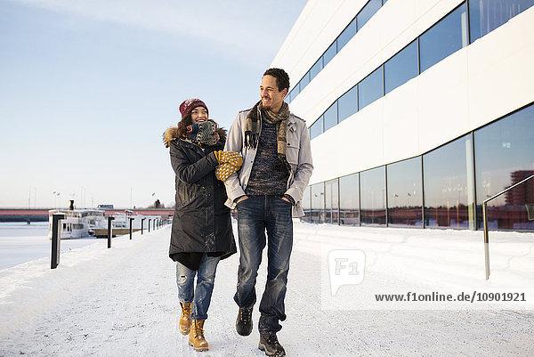 Schweden  Vasterbotten  Umea  Junges Paar  das im Winter am Flussufer entlang läuft.