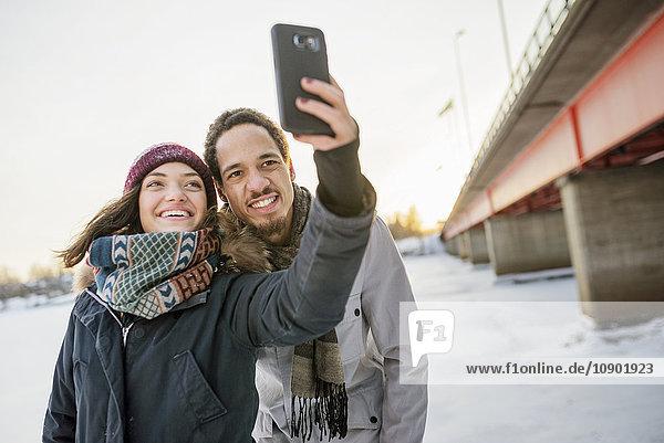 Schweden  Vasterbotten  Umea  Junges Paar  das im Winter Selfie über die Brücke nimmt.