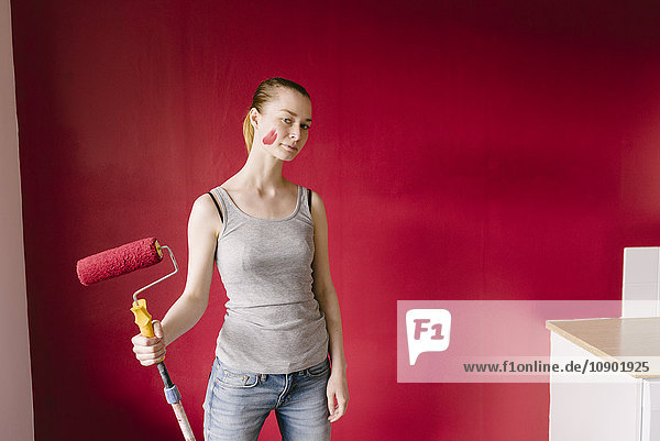 Sweden,  Portrait of woman with paint roller against red wall