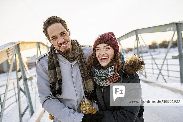 Schweden  Vasterbotten  Umea  Junges Paar auf Fußgängerbrücke im Winter