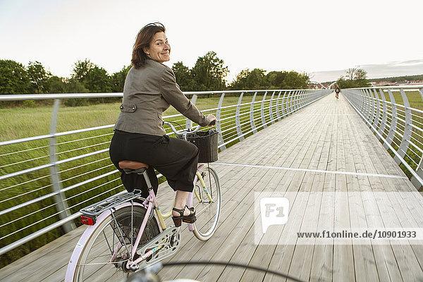 Sweden  Blekinge  Solvesborg  Mature woman riding on bicycle