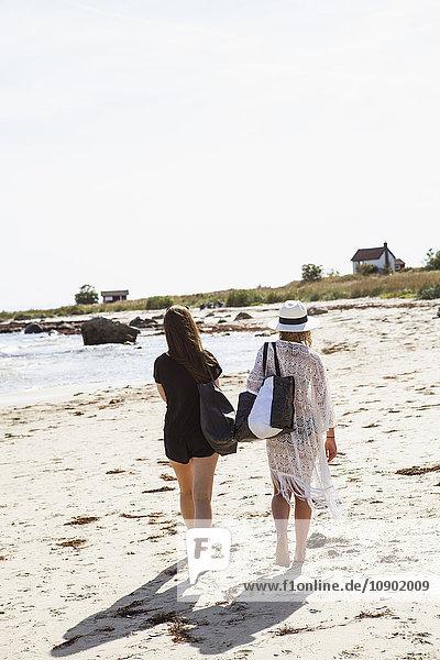 Schweden  Skane  Ahus  Rückansicht von Mädchen (14-15  16-17)  die am Strand spazieren gehen.