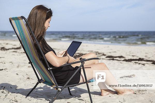 Schweden  Skane  Ahus  Teenage girl (16-17) mit digitalem Tablett am Strand