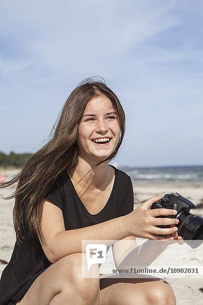 Schweden  Skane  Ahus  Teenage girl (16-17) beim Fotografieren am Strand