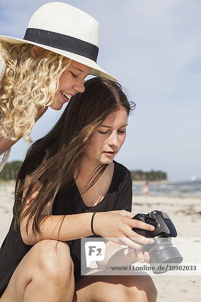 Schweden  Skane  Ahus  Teenage Girls (14-15  16-17) beim Betrachten von Bildern vor der Kamera
