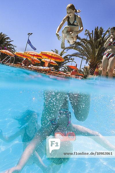 Italien  Sardinien  Alghero  Mutter beobachtet Kinder (14-15  16-17) beim Eintauchen ins Schwimmbad