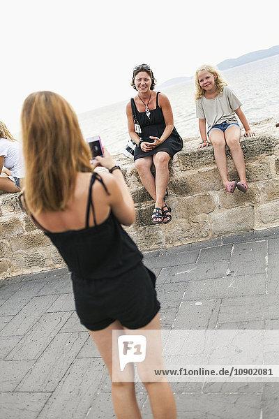 Italien  Sardinien  Alghero  Mädchen (16-17) beim Fotografieren von Mutter und Schwester (14-15)  die auf einer Mauer am Meer sitzen.