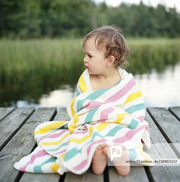 Finnland  Uusimaa  Lapinjarvi  Porträt eines Mädchens (2-3) in Handtuch gewickelt am Steg sitzend