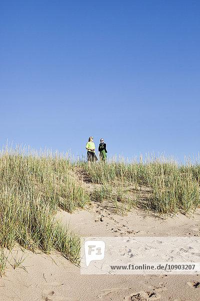 Finnland  Pori  Yyteri  Frauen auf grasbewachsenem Hügel am Strand