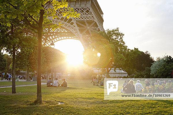 Frankreich  Ile-de-France  Paris  Menschen im Park am Eiffelturm bei Sonnenuntergang