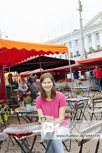 Finnland  Uusimaa  Helsinki  Kauppatori  Porträt einer lächelnden Frau im Open-Air-Restaurant