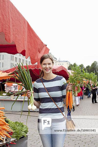 Finnland  Uusimaa  Helsinki  Kauppatori  Porträt einer lächelnden Frau mit Gemüse auf dem Straßenmarkt