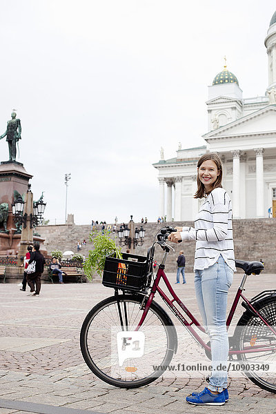 Finnland  Uusimaa  Helsinki  Kauppatori  Porträt einer lächelnden Frau mit Fahrrad am Stadtplatz