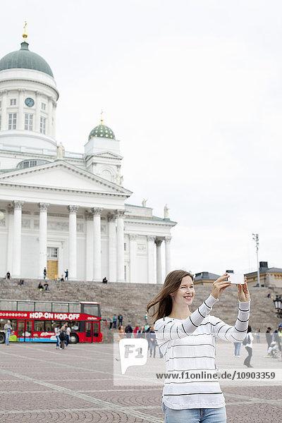 Finnland  Uusimaa  Helsinki  Senaatintori  Junge Frau fotografiert sich selbst mit lutherischer Kathedrale im Hintergrund.