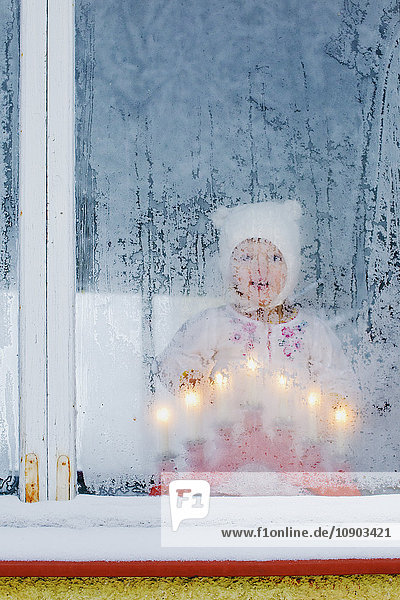 Finland,  Heinola,  Girl (2-3) looking out frosted window