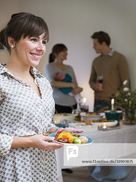 Schweden  Frau beim Essen  Menschen im Hintergrund