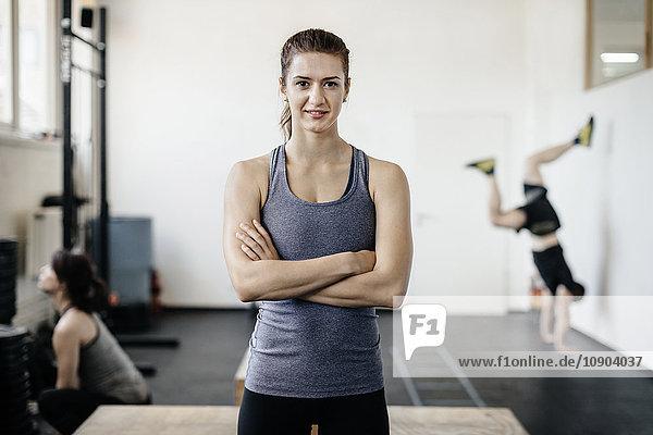 Deutschland  Portrait einer jungen Frau im Fitnessstudio mit gekreuzten Armen