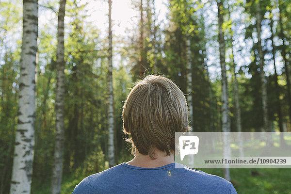 Finnland  Mellersta Finnland  Jyvaskyla  Saakoski  Junger Mann mit Blick auf den Wald