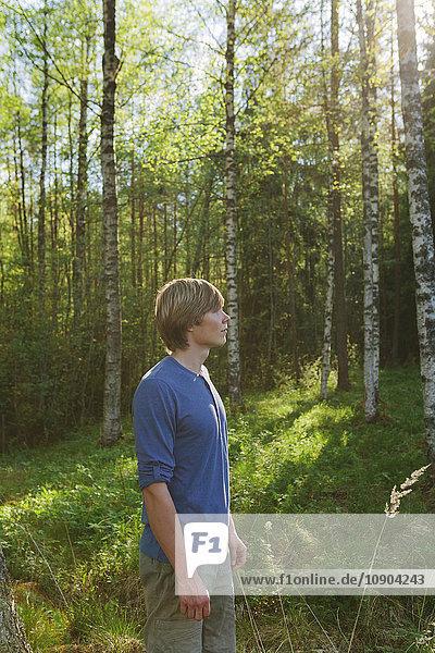 Finnland  Mellersta Finnland  Jyvaskyla  Saakoski  Portrait eines jungen Mannes im Wald stehend