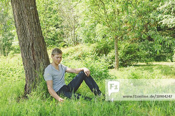 Finnland  Helsinki  Aggelby  Junger Mann im Gras unter dem Baum sitzend