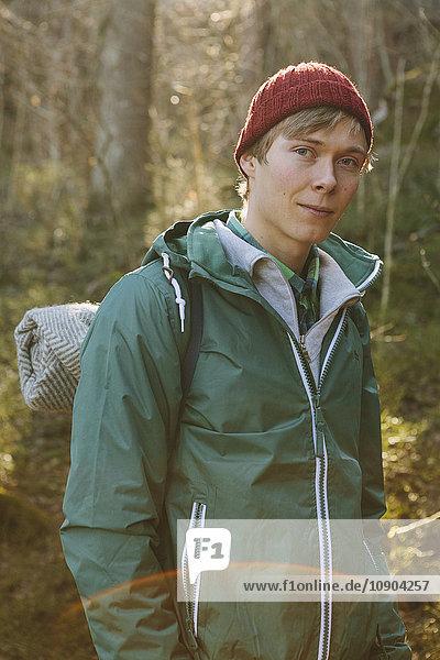 Finnland  Esbo  Kvarntrask  Portrait eines jungen Mannes mit Wollmütze und Windjacke im Wald