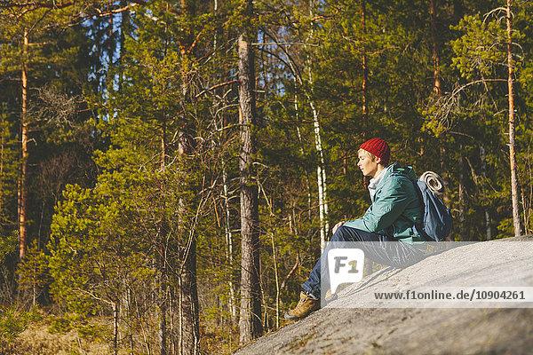 Finnland  Esbo  Kvarntrask  Junger Mann auf Stein im Wald sitzend