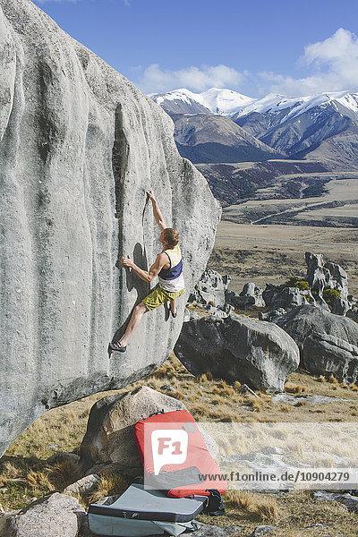 Neuseeland  Castle Hill  Junger Mann klettert mit schneebedeckten Bergen in der Ferne auf den Felsen