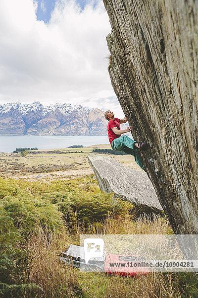 Neuseeland  Queenstown  Lake Wakatipu  Junger Mann klettert die Klippe hinauf