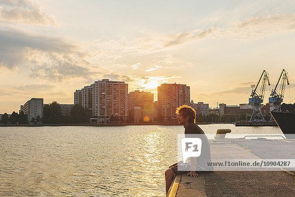 Finnland  Helsinki  Uusimaa  Sompasaari  Mann sitzt am Pier bei Sonnenuntergang