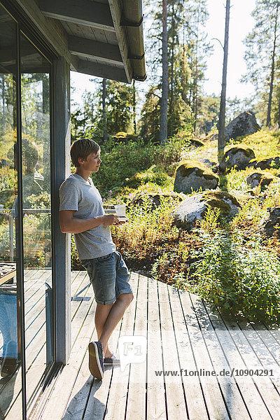 Finnland  Uusimaa  Sipoo  Seitenansicht des jungen Mannes mit Kaffeetasse auf der Veranda