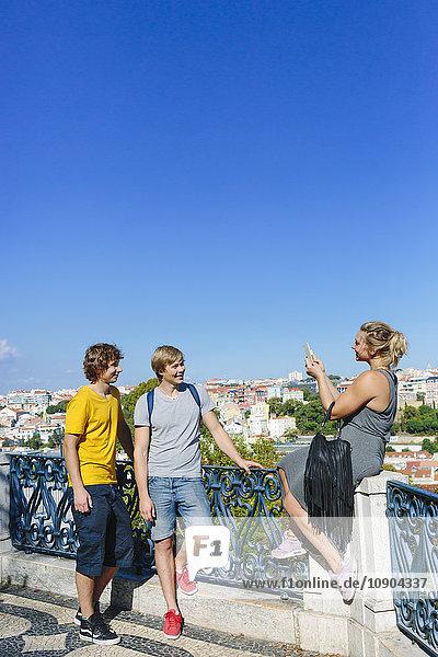 Portugal  Lissabon  Frau fotografiert zwei Männer in der Stadt