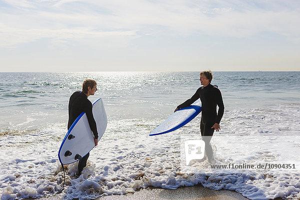 Portugal  Lissabon  Zwei Personen im Wasser stehend mit Surfbrettern