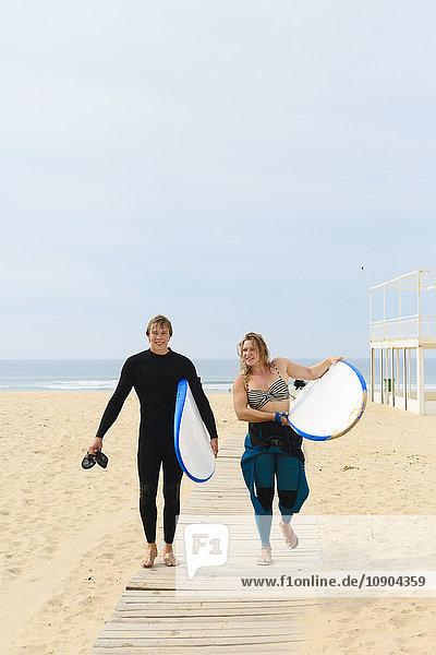 Portugal  Lissabon  Zwei Personen mit Surfbrettern am Strand