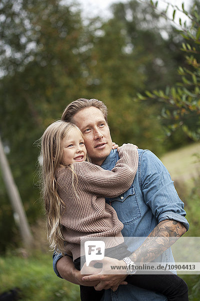 Finland  Uusimaa  Raasepori  Karjaa  Father with his daughter (6-7) looking at view