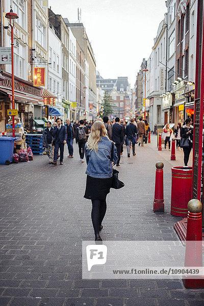 Vereinigtes Königreich  England  London  Rückansicht einer jungen Frau  die die Straße entlanggeht.