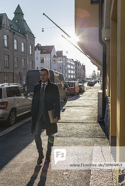 Finnland  Helsinki  Geschäftsmann auf dem Bürgersteig der Stadt