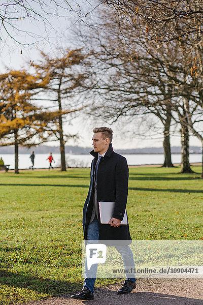 Finnland  Helsinki  Geschäftsmann zu Fuß im Park