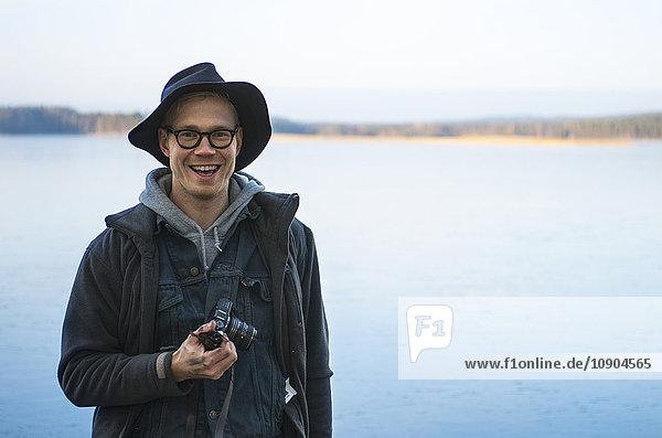 Finnland  Pirkanmaa  Ruovesi  Lächelnder Mann mit Digitalkamera und See im Hintergrund