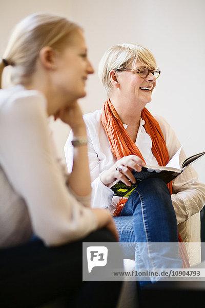 Lächelnde Frau sitzend und mit offenem Buch