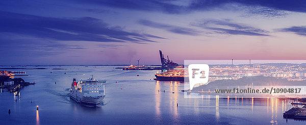 Schweden  Vastra Gotaland  Göteborg  Erhöhter Blick auf beleuchtete Stadt und Hafen bei Dämmerung