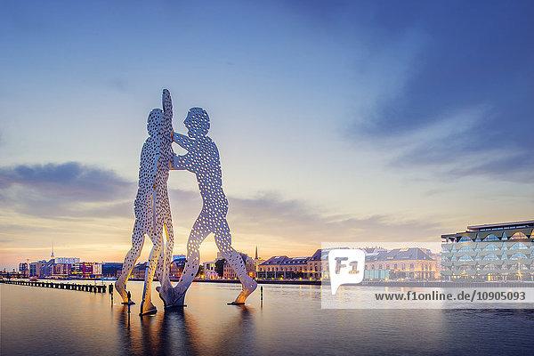 Deutschland  Berlin  Molecule Man Sculpture on Spree und beleuchtetes Flussufer in der Abenddämmerung