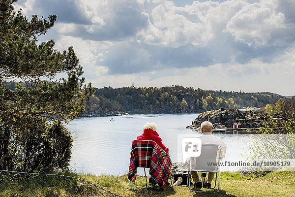 Schweden  Westküste  Bohuslan  Seniorenpaar auf Liegestühlen sitzend und mit Blick auf die Aussicht