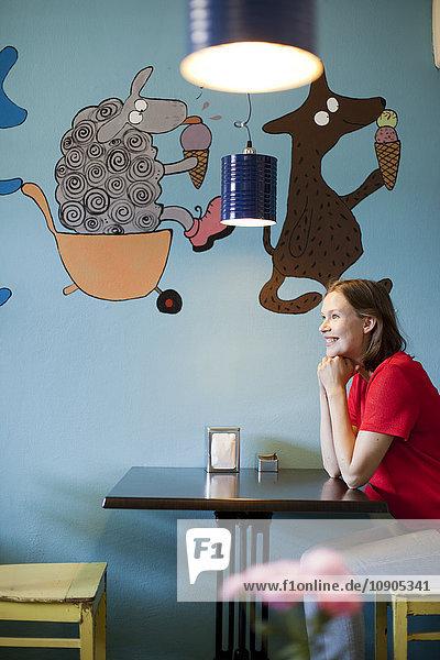 Finnland  Lächelnde Frau sitzt am Tisch im Cafe
